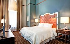 At the Crawford Hotel in Denver Union, this artistically-designed guestroom features a metal headboard upholstered in a Fil Doux, orange base vinyl.