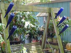 Tall Blue Sherry Bottles on frame of Garden Swing. Need more across the top.