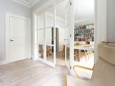 Two small living rooms with a folding glass door seperating them #vahledoor #interiordoor #foldingdoor #glassdoor #bespokedoor #architecture #design #madeindenmark