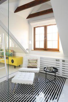 cześć wypoczynkowa obok przeszklonego prysznica. Na tle czarno białej mozaik dumnie prezentuje się fotel i podnóżek Barcelona. kompozycje dopełnia prosty czarny stolik