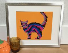 Cat lovers rejoice. A Halloween cat that isnt black. This brightly colored, fuzzy cat, can be the perfect modern Halloween decor but, no one is saying you have to take it down when the holiday is over.  Listing is for PRINT ONLY. Frame, matte, and decorations are not included. Size: 8.5 x 11 hand cut, fits 8 x 10 matting. Paper: Ultra premium presentation paper Ink: black, magenta, bright blue, gray, and olive or orange background  Print is safely shipped in a protective sleeve securely…