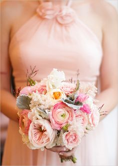 The bridesmaids (in blush dresses) will carry clutch bouquets of pale pink garden roses, blush spray roses, pink astilbe, white ranunculus, and hints of gray dusty miller wrapped in champagne ribbon with the stems showing.