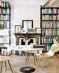 Estilo ecléctico, librerías  de madera sencillas  que rompen el estilo clásico de la chimenea y sillas de diseño que modernizan el ambiente MS