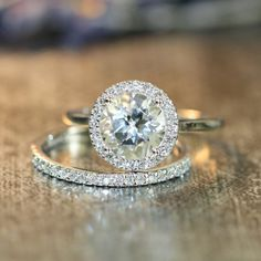 This halo diamond wedding ring set showcases a halo engagement ring with a 8x8mm round shaped natural white topaz crafted in a solid 14k white gold