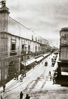 Calle de Monterilla, hoy Cinco de Febrero, vista hacia el sur desde la esquina con Tlapaleros, hoy 16 de Septiembre. A la izquierda, el Palacio del Ayuntamiento, y a la derecha el edificio que tiempo después alojaría a la tienda El Nuevo Mundo. ca. 1900