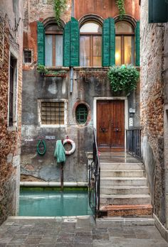 On the other side - Venice, Italy. Photo by Chris Chabot. Teal shutters. Life preserver. Homes on the water.