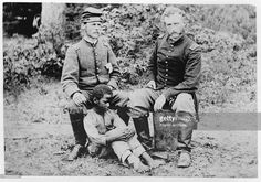 Captain George Armstrong Custer (right) of the 5th Cavalry sits with a Confederate prisoner, Lieutenant James B Washington and his slave, in Fair Oaks, VA, 1862.