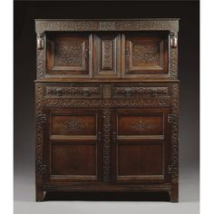 A PRESS CUPBOARD, WILLIAM III, DATED 1701 oak, in two parts carved with strapwork, the frieze with date and initials `RSA', the lower section with two cushion moulded drawers above a cupboard enclosing a shelf, restorations