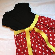 Heres a big girl version of a Bitts&pieces favorite, Minnie Mouse! This dress starts with either a cap-sleeve or long-sleeved Faded Glory t-shirt (WalMart-- these tees are VERY LIMITED until Spring. CONTACT ME before you order.) Minnie is known for her red polka dotted fabric, and it shows up here on her skirt and bow applique. All my big girl dresses are elasticized in the back to make it easy to put on and take off. The yellow grosgrain sash is permanently attached to the front.  This i...