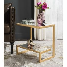 Use this contemporary iron and glass table to create additional storage space in your living room or bedroom, bringing a glamorous touch to your home. Equally at home next to the sofa as a place to perch a cup of tea or in your bedroom displaying a vase of flowers, it is both stylish and versatile. Featuring a gold and white palette and sleek design, it adds a statement feature to any scheme.