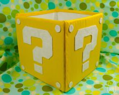 No Sew Mario Block Fabric Storage Cube using cardboard, fabric, & a hot glue gun.