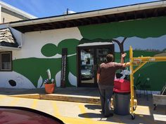 Adam Mueller, 5th Generation Minerva Dairy Butter and Cheese Maker, discussing the progress of the new mural with local artist Bob Strom.