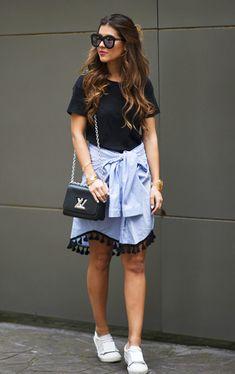 Street style look com camiseta preta, camisa como saia e tênis.