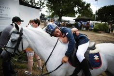 Iwan Carpenter receives  hug from his mum Amanda as he sits on Brookehall Glimpse after competing at the Royal International Horse Show on July 30, 2014 in Hickstead, England.