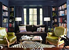 A hi-gloss navy blue pairs well with green leather armchairs in this library designed by Jan Showers - Traditional Home®
