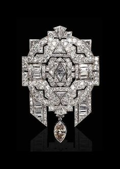 A COLORED AND NEAR COLORLESS DIAMOND BROOCH -  The openwork pavé-set diamond plaque centering upon a navette-shaped diamond, enhanced by baguette and triangular-cut diamonds, suspending a detachable brown marquise diamond, mounted in platinum and 18K white gold.