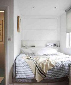 une tête de lit blanche et fonctionnelle avec des étagères et tiroirs