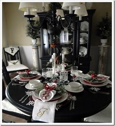 black and white christmas with red accents, monogrammed chair covers and napkins, old columns for plant stands, and snowflake placemats
