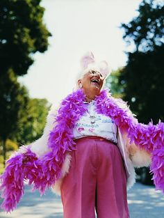 Senior Woman Wearing a Feather Boa and a Rabbit Costume Laughing and Looking Upwards