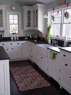 white cabinets, white farmhouse sink, black countertops, natural light