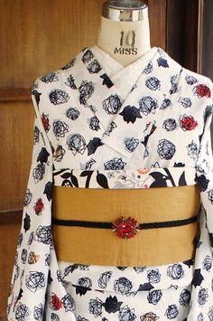 白の地に黒のラインでデザインされたモダンでアートな薔薇のモチーフに、アプリコットベージュや赤、グレーが優しく重ねられたレトロキュートな注染の浴衣です。