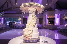 Tall white brides wedding cake on silver cake stand with white flowers cascading down cake - Photo by TRU Identity Photography + Designs