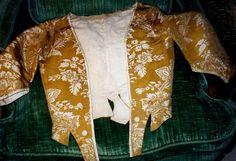 Caraco en damas bicolore, XVIIIe siècle. Dessin à pointe de motifs floraux blancs sur fond taffetas cannelle vers 1740. Manches ¾ coudées, devant à pointe à basques découpées, boutons et bordures galonnées d'un biais de satin blanc (modifications probables)
