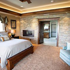 Bedroom design by Pahlisch Homes, Inc...LOVE the stone wall, fireplace, wood trim and accent lighting near the ceiling. Needs some more color or a patterned comfortor in my opinion