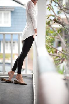 loose white long in the back long sleeve shirt with black leggings and flats.