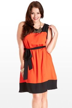 This adorable tunic dress is the colorblocking trend at its best. You'll love the black toke and wide hem, a stirring contrast to the rich lipstick orange-red body. Sleeveless with an easy A-line skirt, black tie sash, and elastic waist, the cut is figure-flattering and comfortable. Pair with colorblocked accessories, black pumps, and an eye-catching necklace.
