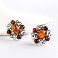 """""""Honey And Cognac Clip-On Amber Earrings Item No. AM01579A01 $31.49 These clip-on earrings are made up of four round cognac Amber stones surrounding an oval honey Amber stone set in ornate .925 Sterling Silver, resembling a flower. Lovely!"""" Amber Earrings, Amber Jewelry, Clip On Earrings, Stud Earrings, Amber Stone, Crystals And Gemstones, Cuff Bracelets, Honey, Make Up"""