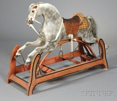 Painted Wood Appaloosa Rocking Horse, America, late 19th/early 20th century, with glass eyes, leather saddle, cut velvet blanket, and horsehair tail, iron-mounted wooden frame painted red with black trim, (loose segments, minor losses), ht. 33 1/2, wd. 16, lg. 44 in.