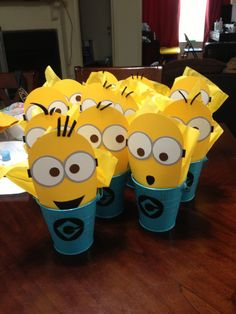 "Despicable me minions party favors filled with candy for the little ones! Blue distressed metal pail. Minions are made with scrapbook paper. ""G"" logo is made of felt. #despicableme #gru #minions #partyfavors #birthday #party #theme #scrapbook #candy"