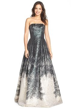 """""""Theia Metallic Jacquard Ballgown Iridescent metallic jacquard textures a snowy forest scene atop this spectacular strapless ballgown. A fitted, princess-seamed bodice defines your figure, while a floor-sweeping skirt releases from the pleated waist for a dramatic, breathtaking finish."""" (quote)"""
