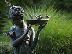 girl statue holding bird bath