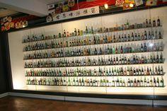 Create a beer bottle display wall behind the bar