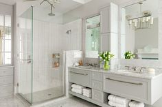 White bathroom with marble countertops and glass showers designed by Castle Design
