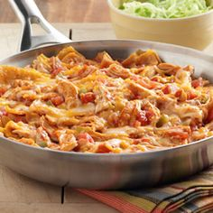 Chicken Enchilada Skillet... A tasty enchillda dish made in just 20 minutes. Featuring cooke chicken, corn, tortillas, cheese and enchilada sauce, this dish is packed full of flavors.