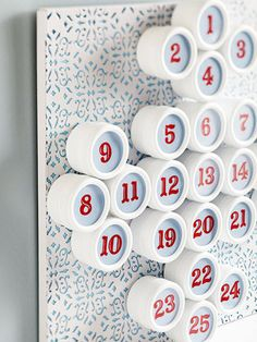 Wall Advent Calendar: a cluster of small lidded storage containers, painted with numbers on colored paper, cut out and glued to the lids, with a small magnet on the back attached to a painted metal board