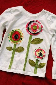 Plain t-shirt transformed into darling top with applique flowers. Would embellish with buttons too. I might even make flowers and leaves in Yo-Yo shapes and add buttons to center of flowers. Sewing Appliques, Applique Patterns, Applique Designs, Embroidery Applique, Sewing Patterns, Embroidery Ideas, Flower Applique, Fabric Crafts, Sewing Crafts