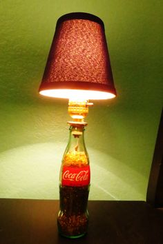 """Glass Bottle Coke Lamp. I bought a lamp kit at Lowes as well as the mini lamp shade. For the """"coke like"""" substance, I went to the craft store and bought two different colors of small rocks that go in flower arrangements. Put the lighter colored rocks on top to replicate the fizz."""