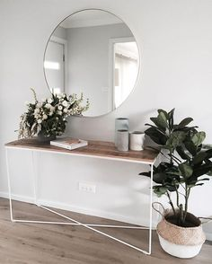 Minimal entry way design - console table with circle mirror and plants