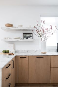 White marble and natural wood kitchen | Cocina en mármol y madera natural con herrajes negros | #MegCassidy #OpenSpaceKitchen #WhiteMarble #NaturalWood #BlackHardware #HuacalEstudioInspo