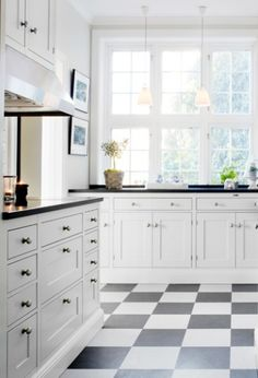 white cabinets, w/ black counters, b&w tile floors