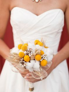 Wedding bouquet with dried yellow craspedias, cotton, tallow berries, phalaris grass, wheat, and sola-wood roses, finished with a mesh collar and a cotton ribbon wrap.