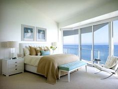 A white Barcelona Chair and a beautiful view in this white bedroom