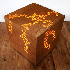 When the light is off they appear to be solid cubes, but once the light is turned on, pattern eminates warmly through the smooth exterior, giving the effect of a projection. Glowing teardrops flow down the sides of this cube.As products are handmade, lead time can vary. Please allow 8 weeks for delivery. Although we endeavor to get them to you as soon as possible.If you would like to commission a larger size, a different veneer or a new and unique pattern, please get in touc...