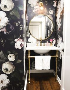 Floral wallpaper in bathroom with round mirror and gold accents