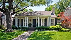 Small cottage ranch with full length front porch black doors and shutters white columns. Perfect