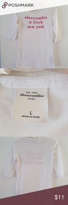 Abercrombie  kids three-quarter sleeve Tee Abercrombie kids size large three-quarter sleeve white t with hot pink lettering. Fits a 10/12. please consider bundling w/ like size/ brand items in my closet!!   Smoke-free pet-free home. Abercrombie Kids Shirts & Tops Tees - Long Sleeve